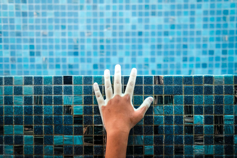 A hand holding the swimming pool deck
