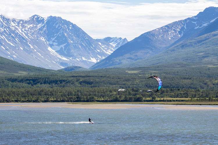Kitesurfing in lake against mountain range