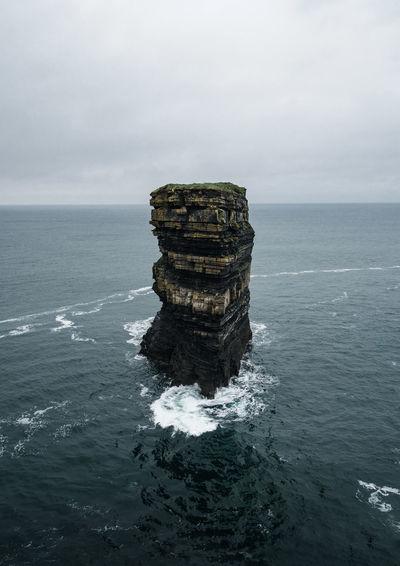 Stack of rock in sea against sky