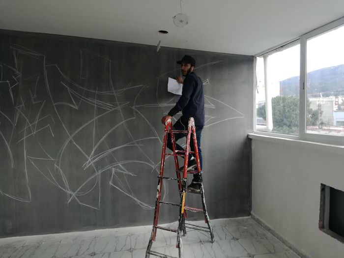 Full length of painter standing on ladder by wall at home