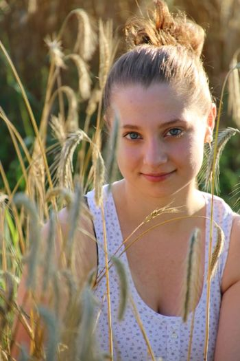 Portrait of young woman smiling by wheat at farm