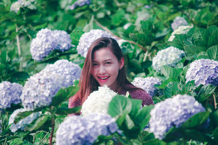 Portrait of smiling woman by flowering plants