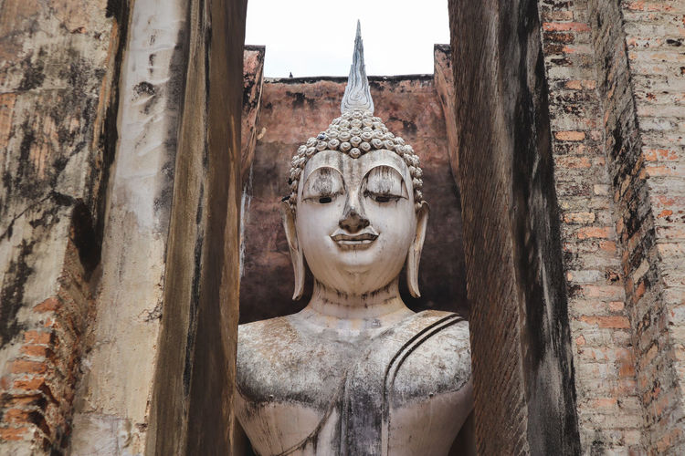 Buddha statue against wall of building
