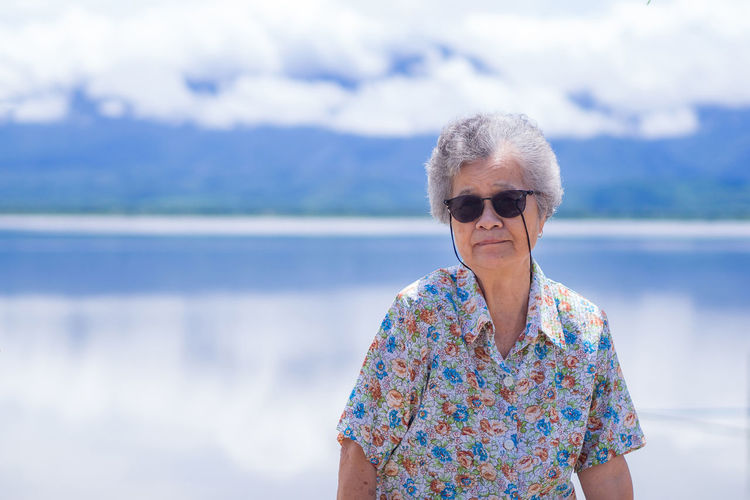 Senior woman wearing sunglasses and sitting on chair side the lake with mountains background.