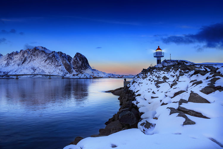 Landscape of Lafoten Islands at winter Lofoten Islands Norway Winter Architecture Beauty In Nature Blue Building Building Exterior Built Structure Cold Temperature Landscape Lighthouse Mountain Nature Night No People North Northsea Outdoors Scenics - Nature Sky Snow Snowcapped Mountain Solid Tranquil Scene Tranquility Water Winter