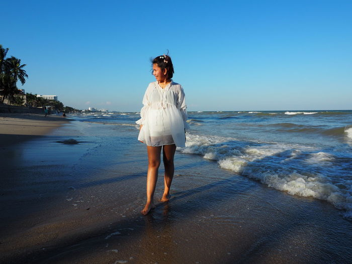 Full length of young woman standing on beach