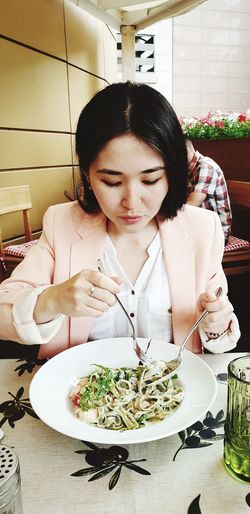 Young woman holding having food while sitting in restaurant