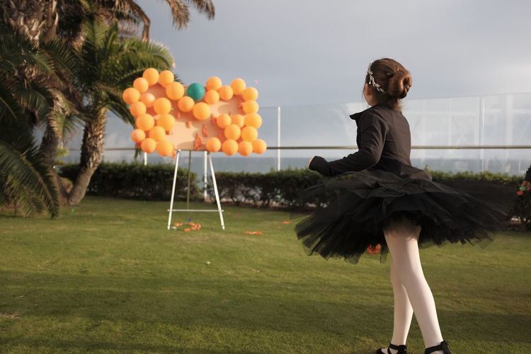 Girl Aiming Balloons While Standing On Grassy Field Against Sky