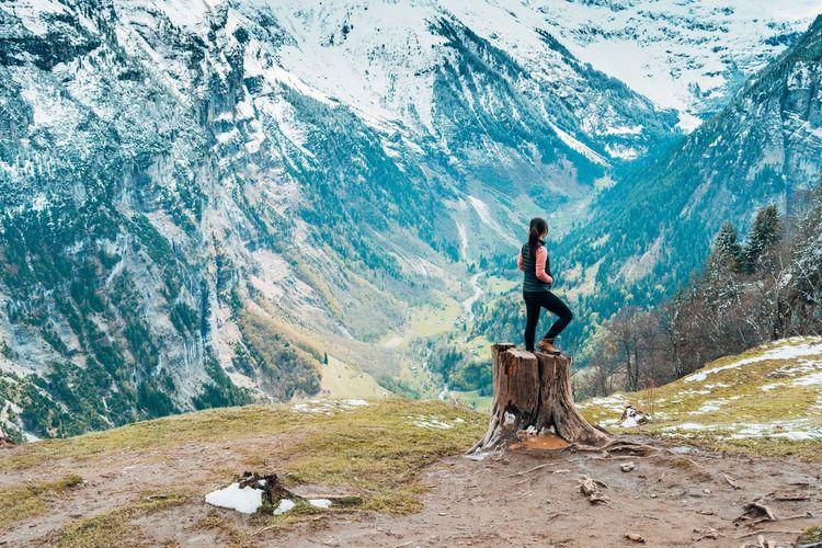 Man standing on field against mountain range