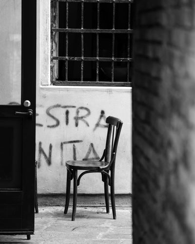 Empty chair against wall