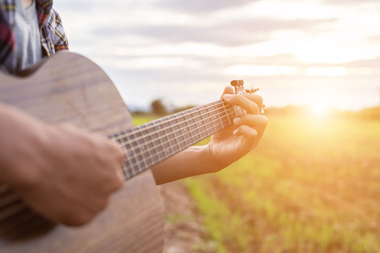 Midsection of man playing guitar on field