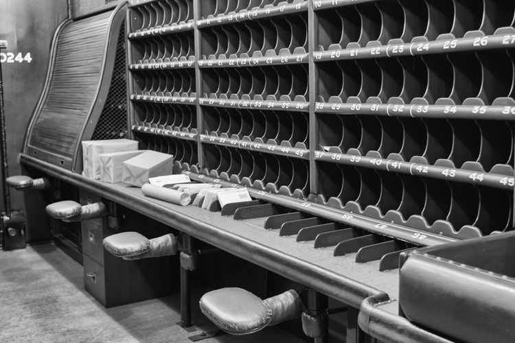 The interior of an old mail train complete with sorting pigeon holes. Preserved at the Bressingham Steam and Gardens, Bressingham, Norfolk. Taken on Nikon D7200, ISO 320, 35mm, f/2.8 1/3 sec, hand held. Mail Train Mail Train Car Seats In Row Arrangement Black And White Enveolopes In A Row Industry Interior Mail Mail Rack Mail Service Mail Sorting Mail Train Interior Museum Parcels Period Pigeon Holes Repetition Shelf Sorting  Still Life Train Vintage Work Place