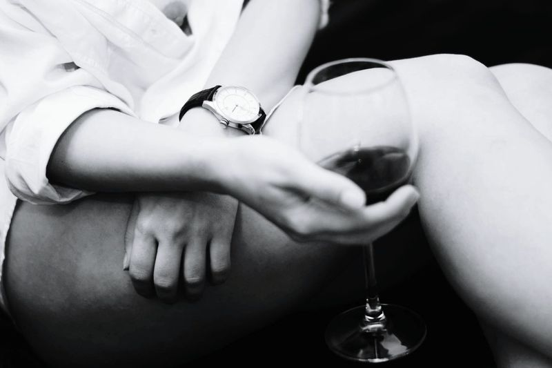 Midsection of sensuous woman holding wineglass