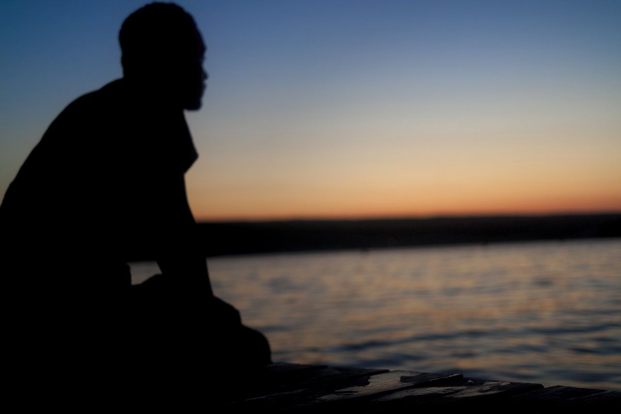 SILHOUETTE MAN SITTING AGAINST SEA DURING SUNSET