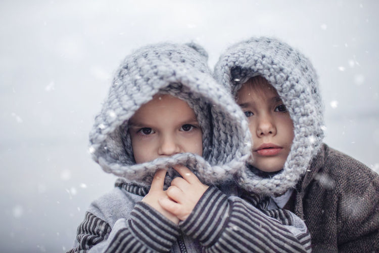 Portrait of sibling standing outdoors during winter