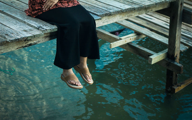 Low section of woman sitting on pier over lake