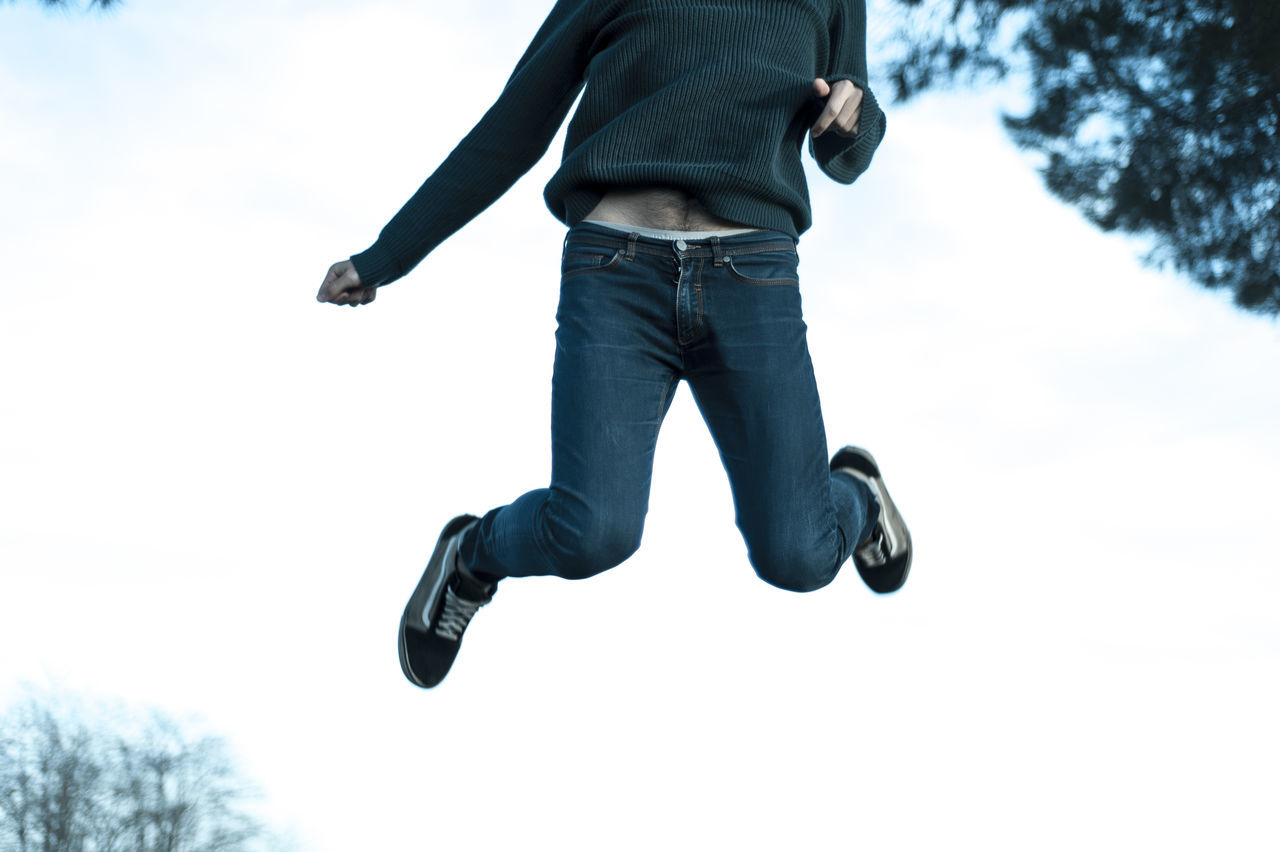 Low section of man jumping on snow