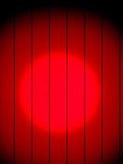 Lit spot on red wooden wall