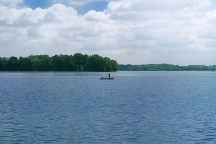 Fisherman in a boat in the middle of a lake Tranquility Trees Beauty In Nature Boat Cloud - Sky Clouds Day Fisherman Fishing Forest Nature Nautical Vessel Non-urban Scene Outdoors Overcast Plant Scenics - Nature Sea Sky Tranquil Scene Tranquility Transportation Tree Water Waterfront Moments Of Happiness