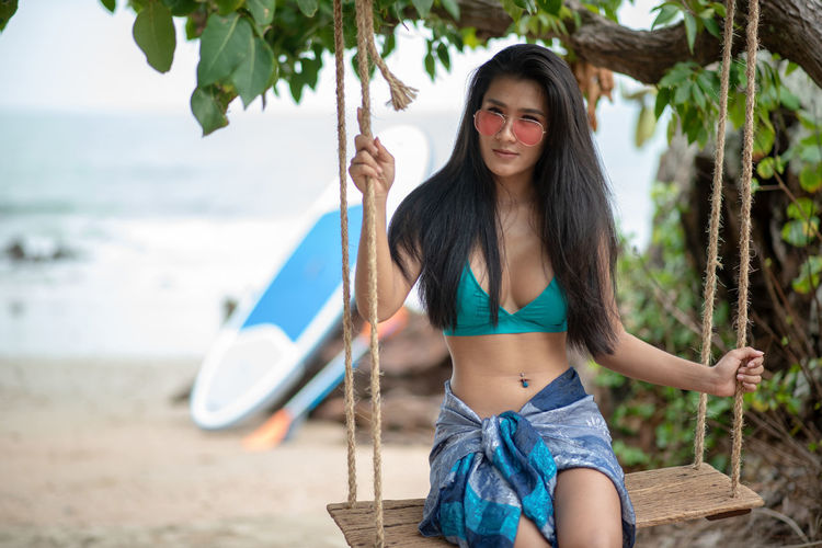 One Person Young Adult Front View Tree Young Women Water Real People Leisure Activity Three Quarter Length Hair Focus On Foreground Lifestyles Day Holding Long Hair Hairstyle Portrait Glasses Sunglasses Beach Beautiful Woman Fashion Outdoors