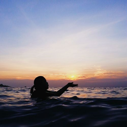 Woman Taking Bath In River During Sunset