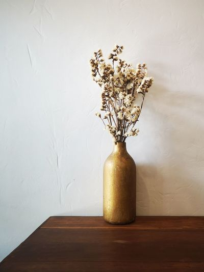 Close-up of white flower vase on table against wall at home
