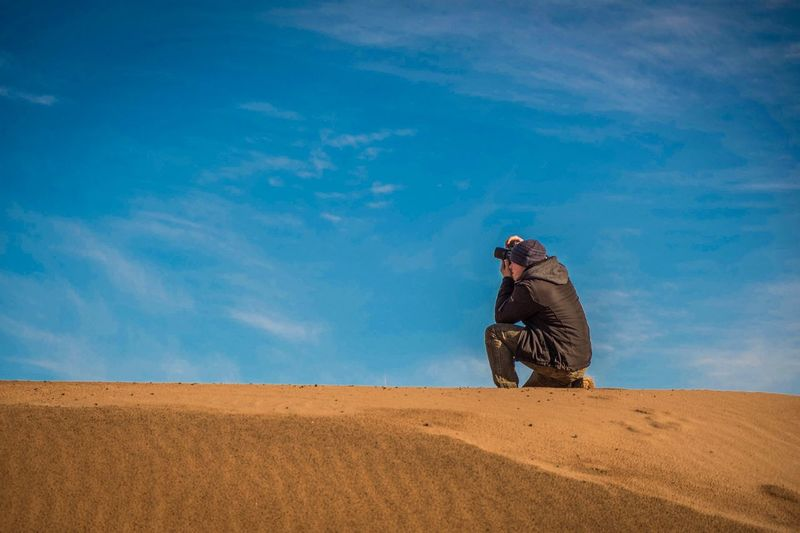 Side view of man photographing with digital camera in desert against sky