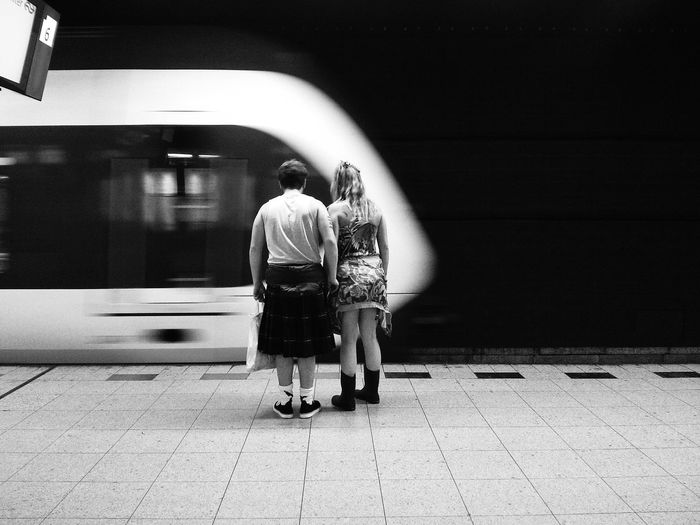 Rear view of man and woman at railroad station