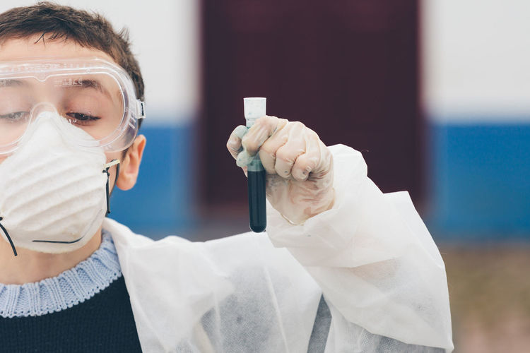 Cropped Image Of Boy Holding Test Tube In Laboratory During Science Project