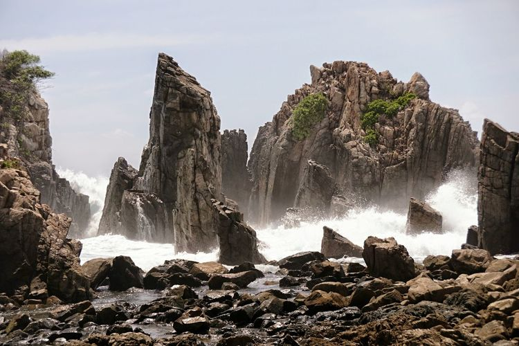 Panoramic view of rocks in sea against sky