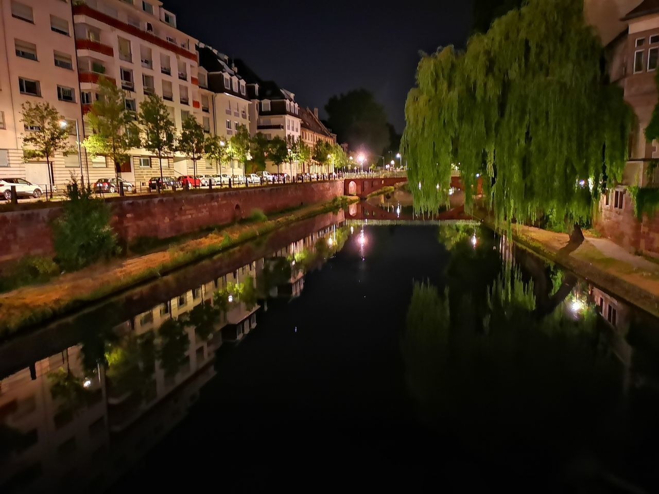 CANAL AMIDST ILLUMINATED BUILDINGS AT NIGHT