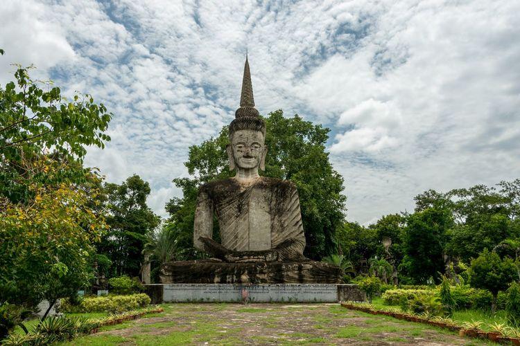 Old Buddha Statue At Sala Keoku Against Cloudy Sky