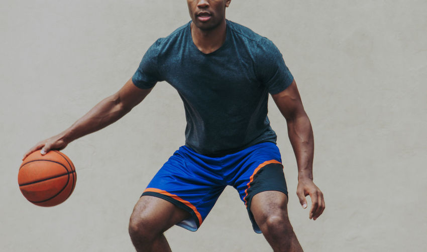 Midsection of young man playing basketball against wall