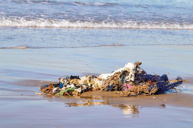 Rubbish, clothing and household stuff washed up from the atlantic ocean on agadir beach, morocco