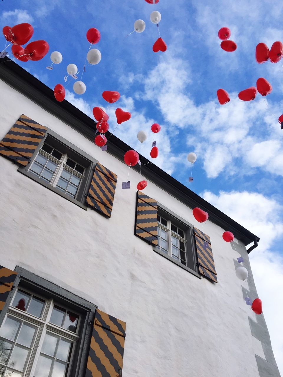 Low Angle View Of Balloons Flying By Building Against Cloudy Sky