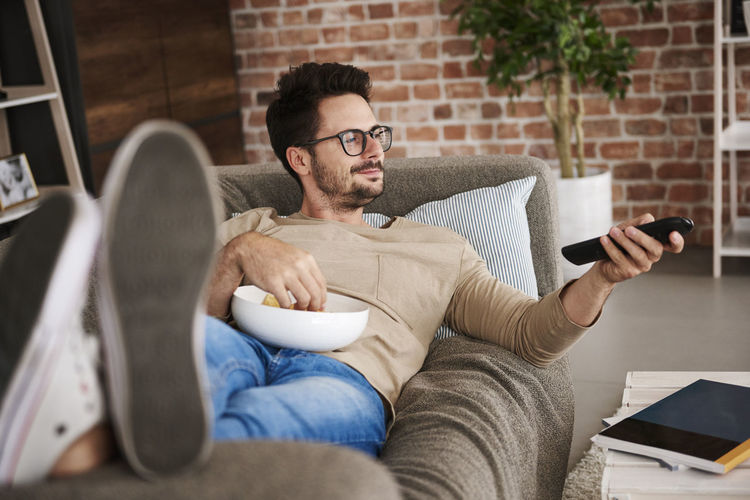 Midsection of man sitting on sofa at home