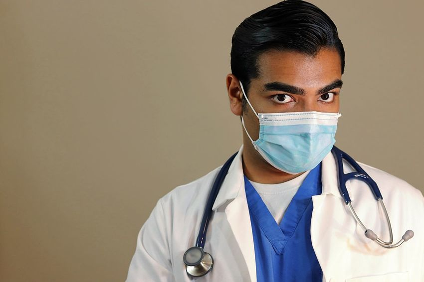Young handsome doctor in blue scrubs and white lab coat looking up Asian  Blue Dentist Doctor  Emergency Equipment Face Mask Gloves Health Healthcare And Medicine Hospital Indian Lab Coat Medical Medicine Nurse Procedure Scalpel Scrubs Spanish Stethoscope  Surgeon Surgery Uniform White Color