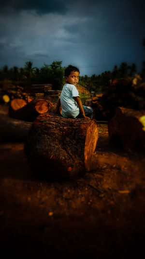 """""""He said chachu take a picture of me"""" EyeEm Best Shots EyeEmNewHere Nature_collection Nature Photography EyeEm Best Shots - Nature Portrait Portrait Photography Portraits Portrait Of A Child Portraits PortraitPhotography EyeEm EyeEm Masterclass EyeEm The Best Shots eyeemphoto Full Length Sitting Child Men Boys Tree Childhood Sky Silhouette Firewood Lumber Industry Evening Timber Outline Woodpile"""