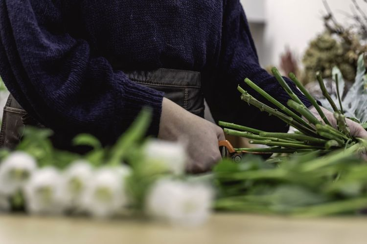 Midsection of person working in flower shop