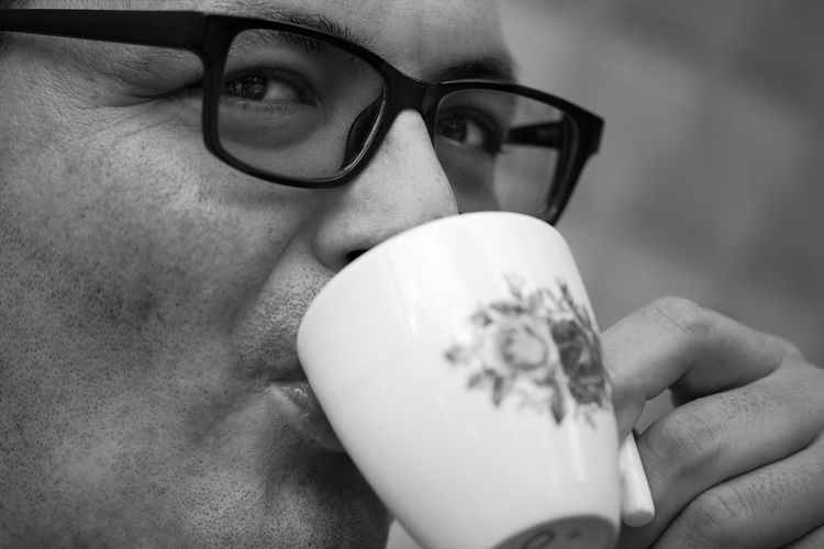 Close-up portrait of man drinking coffee outdoors