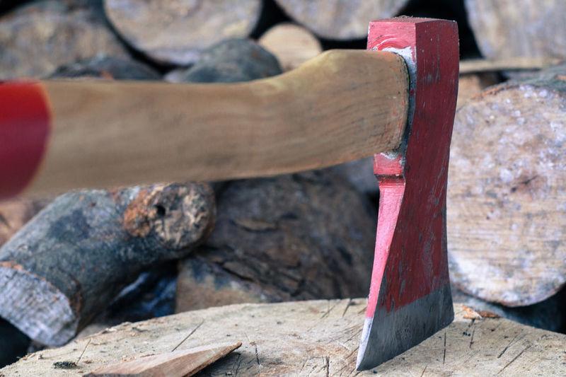 Close-up of axe stuck on tree stump