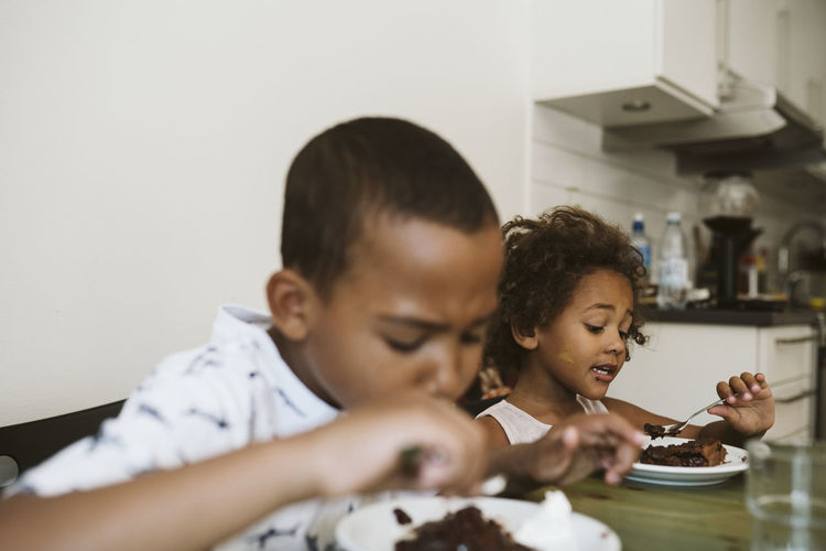 Children of mother and daughter in kitchen