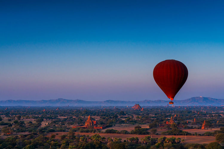 Hot air balloon flying over landscape against blue sky