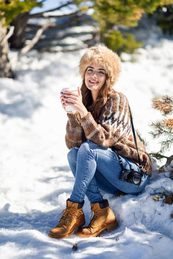 Portrait of smiling woman sitting on snow outdoors