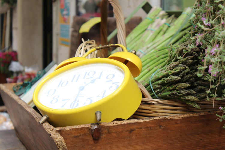 Close-up of alarm clock and vegetables on table