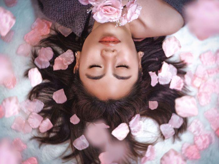 Portrait of woman lying on pink flowers