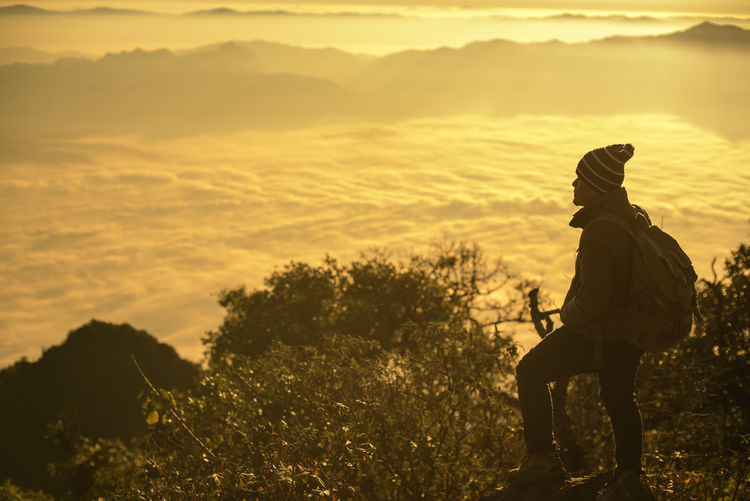 Backpacker Looking At View While Standing On Cliff During Sunset