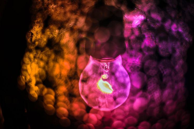 Close-up of illuminated lights hanging on glass