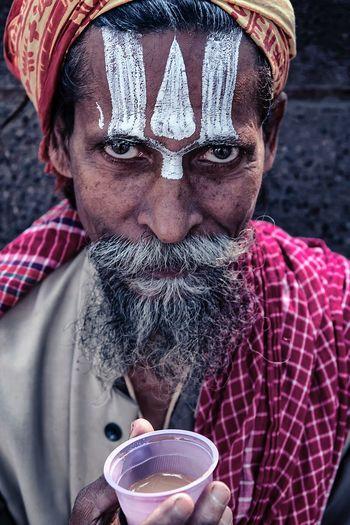 High angle portrait of sadhu holding tea cup