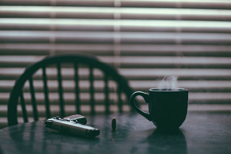 .45 handgun on dining room table alongside a steaming hot cup of coffee